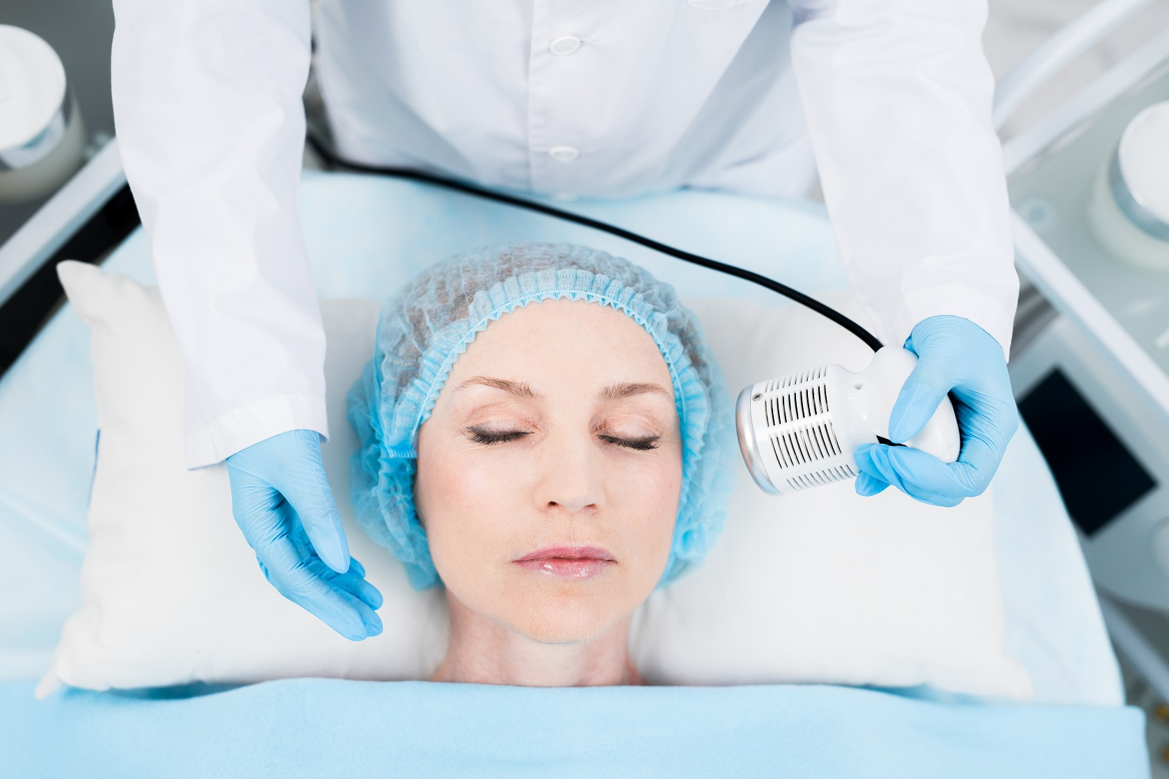 Contemporary beautician using electric device for cleansing skin of client