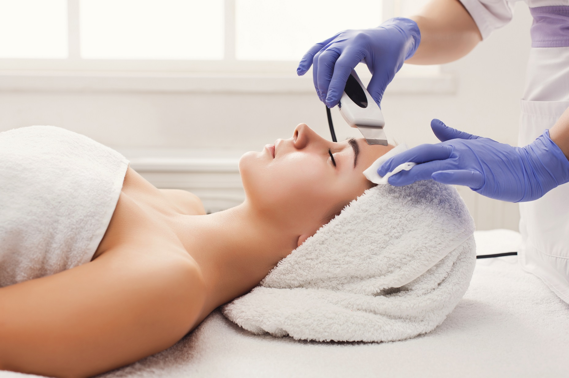 Rejuvenating facial treatment. Model getting lifting therapy massage in a beauty SPA salon. Exfoliation, stimulation and hydratation. Aesthetic cosmetology, closeup, copy space
