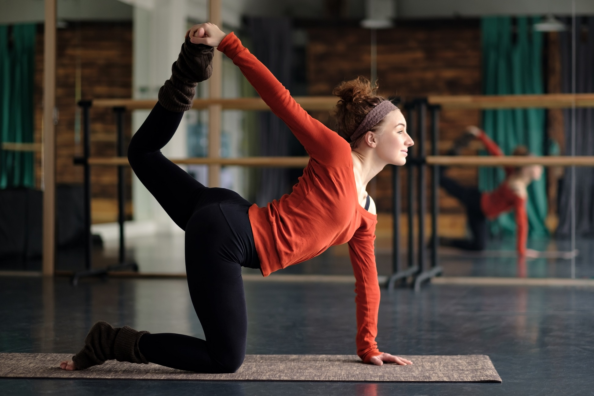 Young woman practicing yoga, stretching in Bird dog exercise, tiger pose, working out. Indoor full length